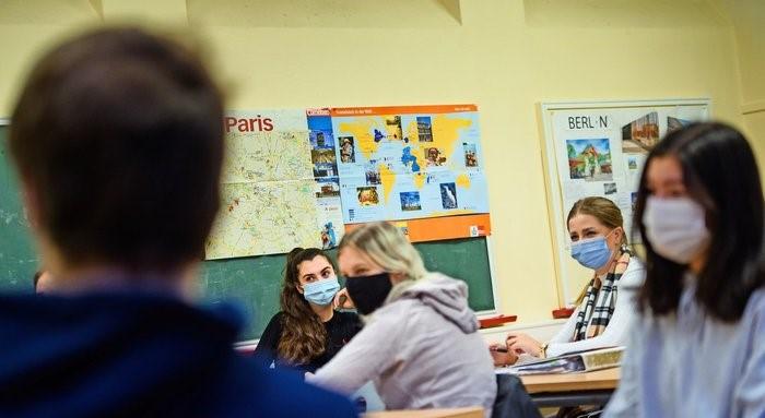 Schülerinnen sitzen sich während einer Unterrichtsstunde an ihren Tischen gegenüber. Foto: dpa